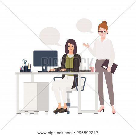 Pair Of Women Working At Office Together. Female Clerks Dressed In Smart Clothes Sitting In Chair An