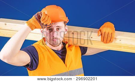 Woodworker Concept. Man In Protective Gloves Holds Visor Of Helmet, Corrects Hard Hat On Head, Blue