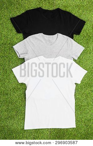 Stack Of Different Coloured Mens T-shirt On Grass Background. Vertical Wiev.