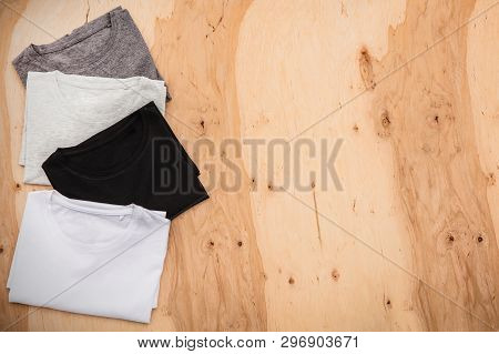 Stack Of Arranged Different Coloured Mens T-shirt On Wooden Background. Horizontal View.