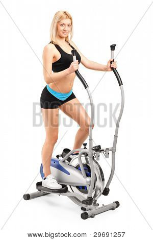 A beautiful woman exercising on a cross trainer machine isolated on white background