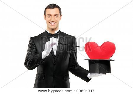 Young magician holding a magic wand and top hat with a red heart shaped pillow in it isolated on white background