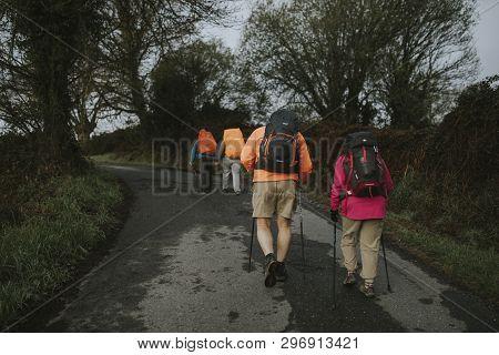 Sarria, Spain - April 7th, 2019: Camino De Santiago Pilgrims Walking With A Backpack Across A Rural
