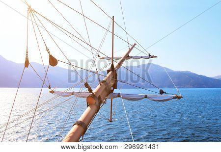 Sunlight at sea on a tall ship classic sailboat. Beautiful landscape with mountains, sea and ship rigging. Cruise on retro ship at lake Ashi, Hakone, Japan