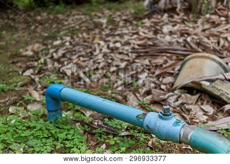 Old Water Valve With Blue Plastic Pipe In Garden With Blur Brown Dry Leaves As Background And Copy S