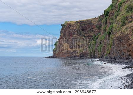 High Rugged Rocky Coastline Against Cloudy Sky In Calheta On Portuguese Island Of Madeira. This Phot