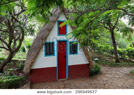 Small Cosy Chalet With A Triangular Thatched Roof In Between Of Green Trees. Portuguese Island Of Ma