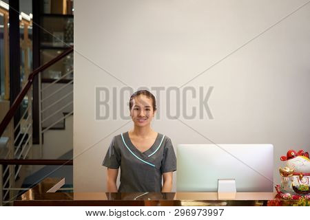 Smiling Attractive Young Asian Receptionist In Gray Uniform Standing At Counter With Computer And Lo
