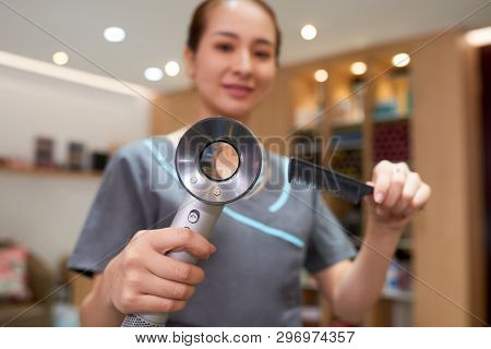 Close-up Of Professional Asian Hairdresser In Uniform Using Modern Hair Dryer And Comb For Hairstyli