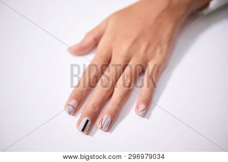 Close-up Of Unrecognizable Woman Holding Hand With Creative Manicure In Black And White Colors On Ta