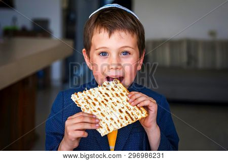 Cute Caucasian Child In A Yarmulke Taking A Bite From A Traditional Jewish Matzo Unleavened Bread In