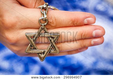 A Hand Of A Young Woman Holding A Key Chain With A Star Of David, Traditional Jewish Symbol. A Conce