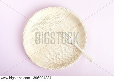 Biodegradable Bamboo Plate With Fork On Light Pink Background