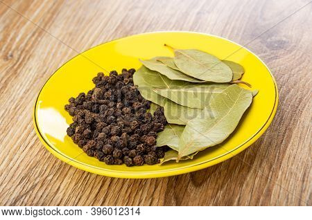 Peppercorn And Dried Bay Leaves In Yellow Plate On Wooden Table
