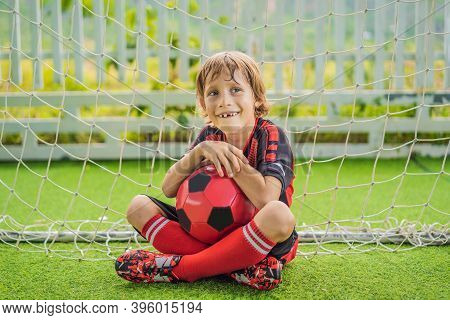 Little Cute Kid Boy In Red Football Uniform Playing Soccer, Football On Field, Outdoors. Active Chil