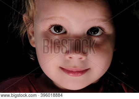 Child's Face Close Up In The Dark, Concept Mystery In The Child's Soul ,soft Focus And Light Blur