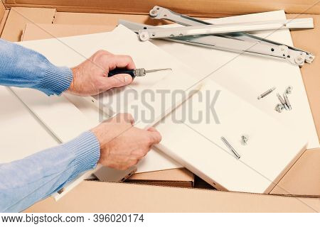 Man Unpacks And Assembles Flat Packed Furniture Isolated. Box With White Diy Funiture And Hands With