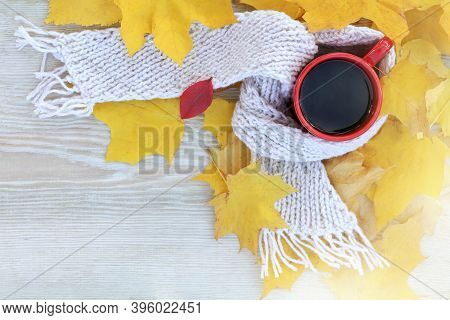 Coffee In A Red Mug With A White Scarf In Yellow Leaves Top View. Warming Autumn Drink