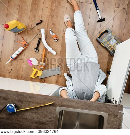 Woman Fixing Kitchen Sink. Housewife Working Under Kitchen