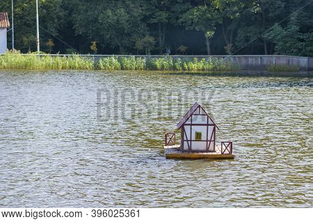 Wooden House For Duck On Water. Artificial Housing For Wild Birds On The City Lake. Selective Focus.