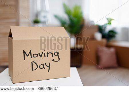 Moving Day And Relocation Concept - Cardboard Boxes In New House After Moving Day