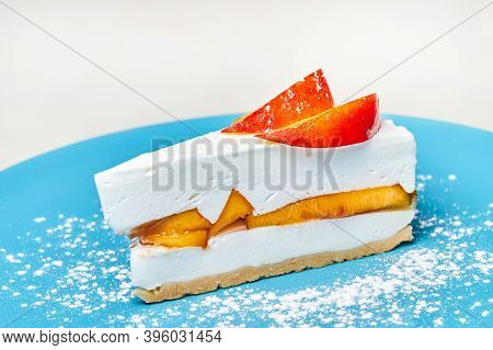 Yoghurt Cheesecake With Peaches On The Blue Plate