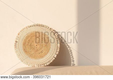 Round rattan paper plate holder by a beige wall