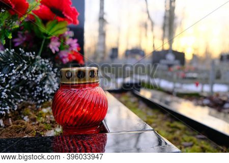 Red Glass Candle Lattern On The Grave. Sunset Background With Blurred Cemetery.