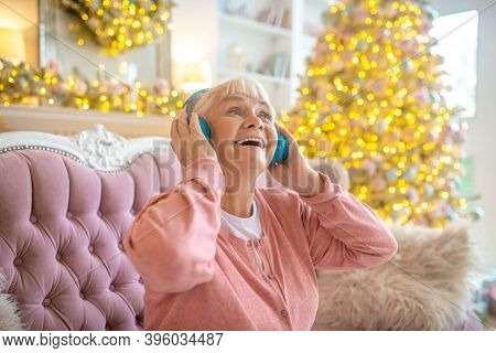 Grey-haired Woman Listening Music In Headphones And Feeling Delighted