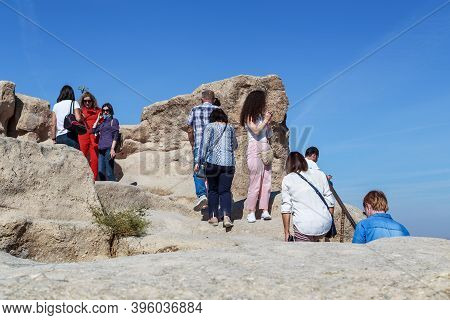 Uchisar, Turkey - October 4, 2020: Unidentified People Climb A Top Of The Tuff Rock (uchisar Castle)