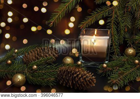Christmas Beautiful Branches And Cones, A Burning Candle On A Dark Background. Christmas Decor