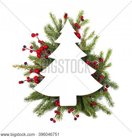 Christmas white fir tree shaped blank card with copy space and decor of fir tree branch red holly berry isolated on white background