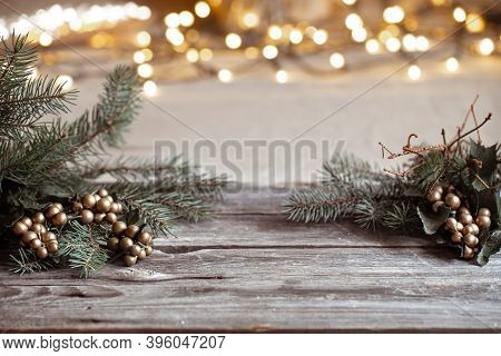 Christmas Background With Branches Of A Christmas Tree On A Wooden Table And Blurred Bokeh Lights.