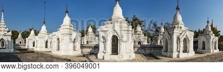 Kuthodaw Pagoda contains the worlds biggest book. There are 729 white stupas with caves with a marble slab inside - page with buddhist inscription. Panoramic photo. Mandalay, Myanmar
