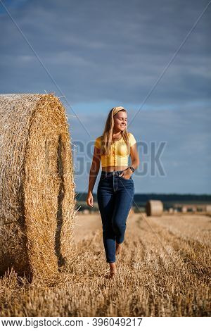 A Young Beautiful Blonde Stands On A Mown Wheat Field Near A Huge Sheaf Of Hay, Enjoying Nature. Nat
