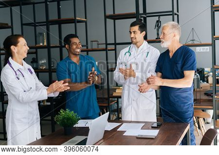 Successful Happy Gray-haired Mature Male Chief Doctor Leader Get Team Applause In Light Office Room