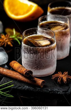 Shot Glass Of Herb Liqueur With Cinnamon And Oranges On Dark Background. Alcoholic Booze Cocktail. G