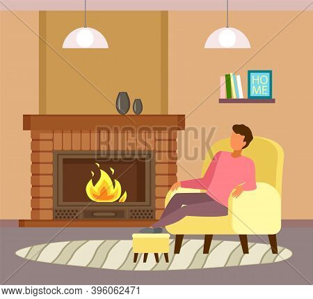 Man Sitting At Armchair Near Fireplace And Relaxing. Guy Enjoy Leisure Time, Like Spend Time At Home