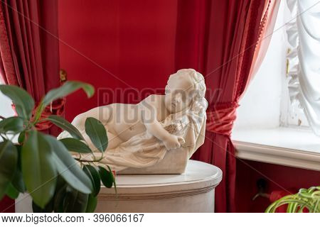 Sculpture Of Angel In Museum. Close Up Of White Sculpture Of Child On Background Of Red Wall And Cur