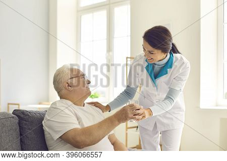 Smiling Nurse Giving Glass Of Water To Senior Man In Nursing Home Or Assisted Living Facility