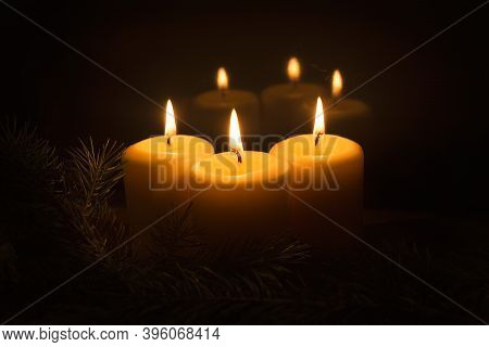 White Candles With Fir Branches On A Dark Background. The Flame Of Three Candles Is Reflected On A D
