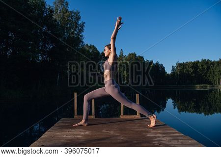 Girl Is Practicing Yoga Technique On The Pier By The Lake And Meditating. Meditation To Purify Mind