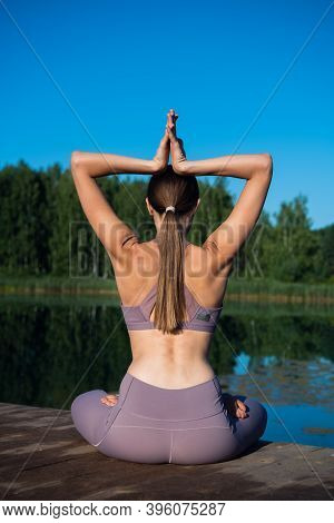 Woman Sitting In Lotus Position And Doing Yoga On A Forest Lake. Beautiful Girl Doing Exercises On S