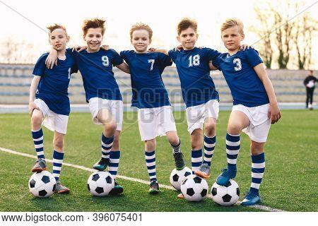 Sporty School Boys In Soccer Team. Group Of Children In Football Jersey Sportswear Standing With Bal