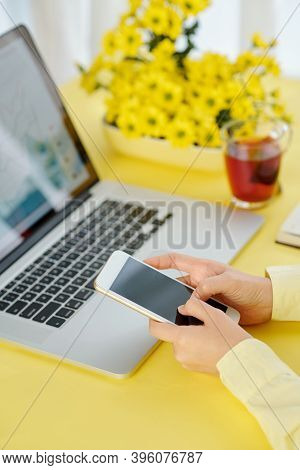 Close-up Iamge Of Businesswoman Sitting At Office Deak And Using Mobile Application On Smartphone