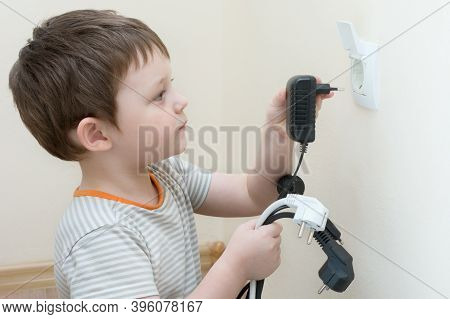 He Child Plays With Electric Plugs, Holds Several Plugs In His Hands And Tries To Insert Into The So