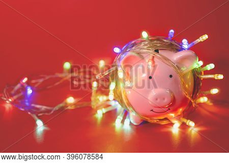 Pink Piggy Bank With Christmas String Lights On Happy December Festival In Red Background, Enjoy Sav