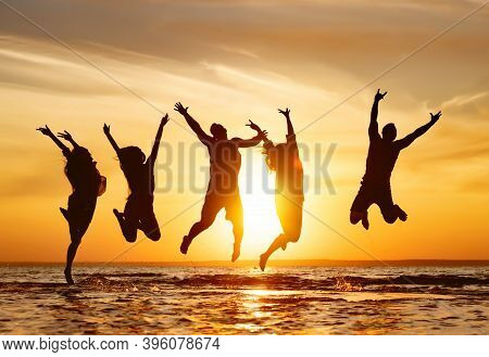 Silhouettes Of Five Happy Jumping Friends In Water At Sunset Time
