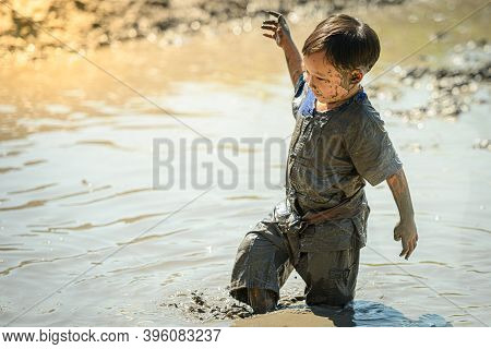 Child Asian Boy Playing Mud In Cornfield On Sunny Day. Thai Asia Children Play Getting Dirty While I