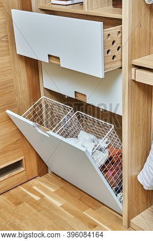 Modern Wardrobe With Opened Metal Mesh Laundry Basket And Wooden Drawers. Wooden Wardrobe With Light